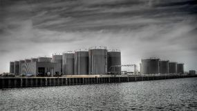Fuel silos on docks. Fuel silos on docks by the water in black and white Stock Photos
