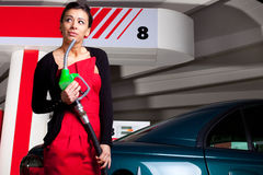 Fuel station woman. Young woman pumping fuel in her car on gas station royalty free stock photo