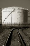 Fuel Storage Tank. Sepia image of railroad tracks curving in front of a fuel storage tank/silo royalty free stock photos