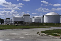 Fuel Storage Tanks. A group of fuel storage tanks with a bright blue sky with clouds Royalty Free Stock Photos