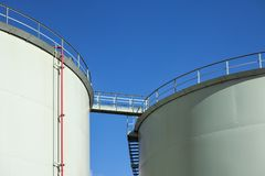 Fuel storage tanks with catwalk bridge against blue sky. Fuel storage tanks with catwalk bridge against a blue sky royalty free stock photo