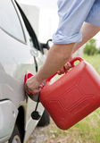 Fuel tank. Man refilling his car with funnel and red tank fuel Stock Photos