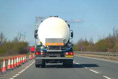 Fuel tanker on dual carriageway. Rear view of a fuel tanker driving along a dual carriageway Royalty Free Stock Image