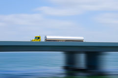 Fuel tanker semi truck on bridge with motion blur. Eighteen wheeler semi tractor truck tanker pulling a petroleum fuel tank over a bridge with a motion blur Stock Photos