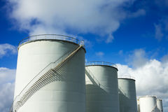 Fuel tanks. Wight metal industrial Fuel Tanks and a blue sky Royalty Free Stock Photography