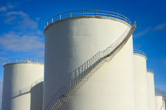 Fuel tanks. Industrial metal white fuel tanks with stairs and blue sky Royalty Free Stock Photo