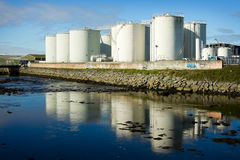 Fuel tanks on the bank of the river Stock Photos