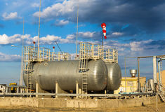 Fuel tanks and pipe-line for boiler-house on industrial site. Capacities for fuel on a production site against the cloudy sky Stock Photography