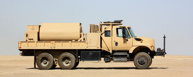 A fuel truck. A military desert color fuel truck on a clean sky background stock image