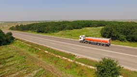 Fuel Truck Driving On Country Road. AERIAL VIEW. Camera is slowly moving sideward demonstrating rural landscape - fuel truck driving fast along country road with stock footage