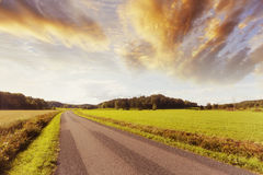 Lonely country road at sunset Stock Image