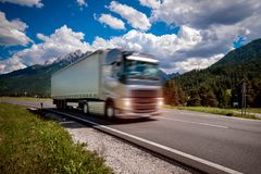 Fuel truck rushes down the highway in the background the Alps. T Stock Photos