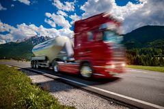 Fuel truck rushes down the highway in the background the Alps. T Stock Photography