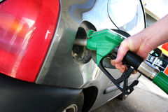 Fueling car. Petrol or gasoline fueling, refuel or refilling car, hand holds nozzle whilst putting fuel in car at petrol or gas station royalty free stock image