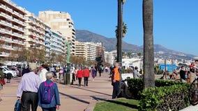 FUENGIROLA, ИСПАНИЯ - 7-ОЕ АПРЕЛЯ 2019: Люди и турист идя на известную прогулку Paseo Maritimo, старший человек разрабатывая видеоматериал