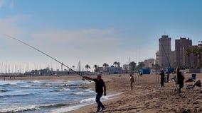 Fuengirola, Spagna - 6 aprile 2019: Un pescatore che pesca sulla spiaggia un giorno ventoso video d archivio