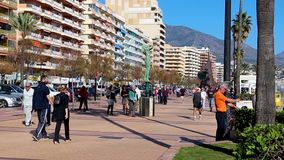 FUENGIROLA SPANIEN - APRIL 7, 2019: Folk och turist som g?r p? ber?md Paseo Maritimo promenad, ?ldre man som utarbetar arkivfilmer