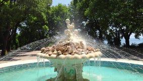 Fuente con la estatua de los ángeles en un parque del jardín del mar con la hierba y árboles alrededor de ella en Varna, Bulgaria almacen de video