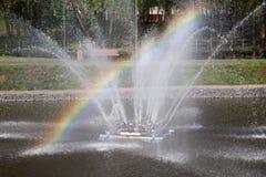 Fuente con un arco iris en el parque de la ciudad fotos de archivo libres de regalías