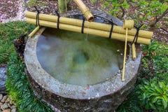 Fuente de agua de Tsukubai en jardín japonés en Kita-en el templo, Kosenbamachi, Kawagoe, Saitama, Japón en primavera Con el arou Imágenes de archivo libres de regalías