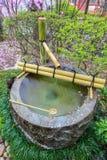 Fuente de agua de Tsukubai en jardín japonés en Kita-en el templo, Kosenbamachi, Kawagoe, Saitama, Japón en primavera Con el arou Imagen de archivo