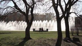 Fuente de la ciudad cantidad Gente que recorre en el parque Fuente en parque de la ciudad en día de verano caliente Corriente del almacen de metraje de vídeo