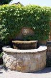 Fuente de la piedra decorativa cerca de la pared Foto de archivo