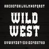 Fuente del oeste salvaje Alfabeto del vintage Letras y números ásperos en un fondo de madera del grunge Foto de archivo