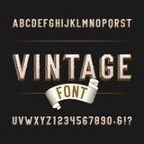 Fuente del oeste salvaje del alfabeto del vintage Letras y números apenados del efecto en un fondo oscuro Fotos de archivo