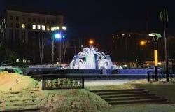 Fuente en el invierno, con la iluminación del Año Nuevo de la noche Fotografía de archivo libre de regalías