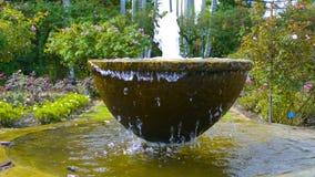 Fuente en el jardín rodeado por naturaleza almacen de metraje de vídeo