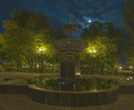 Fuente en parque de la noche en las linternas y la luna del cielo Foto de archivo libre de regalías
