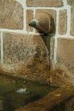 Fuente hecha de piedra con un pequeño canalón de agua imagen de archivo libre de regalías