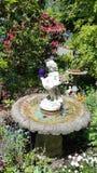 Fuente hermosa del jardín de la querube con las flores salvajes imagenes de archivo