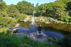 Fuente hermosa en el medio de un río rocoso ancho en el fondo de árboles verdes densos Fotos de archivo