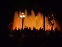 Fuente mágica Barcelona España de la silueta de la gente Foto de archivo