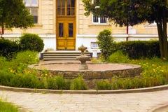 Fuente vieja en el patio trasero rodeado por las flores Imagenes de archivo