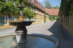 Fuente y apartamentos en el Fuggerei en Augsburg foto de archivo