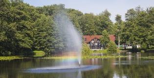 Fuente y arco iris hermosos en un lago Foto de archivo