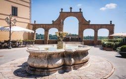 Fuente y arcos antiguos en el cuadrado de Repubblica, en Pitigliano Imagen de archivo libre de regalías