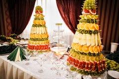 Fuente y decoraciones de Champán de la fruta en la tabla que fija a Foto de archivo libre de regalías