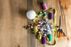 Fuentes de costura, carretes del hilo, botones, tijeras, midiendo Imagen de archivo
