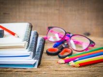 Fuentes de escuela coloridas con los libros, los lápices del color, los vidrios rosados, la pluma y el cortador en fondo de mader Imagenes de archivo