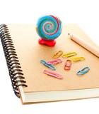 Fuentes de escuela con el globo, el clip y el cuaderno del arte en la parte posterior del blanco Foto de archivo