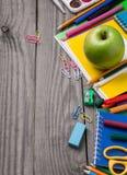 Fuentes de escuela con la manzana verde en la tabla de madera Foto de archivo libre de regalías