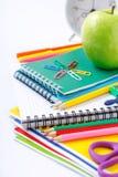 Fuentes de escuela con la manzana y el despertador verdes Fotos de archivo