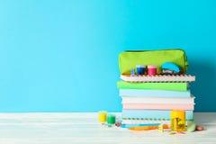 Fuentes de escuela en la tabla de madera contra fondo del color foto de archivo