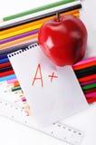 Fuentes de escuela en un fondo blanco con una manzana y con una n Imagen de archivo libre de regalías