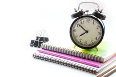 Fuentes de escuela, libro y despertador coloridos en blanco Cierre para arriba De nuevo a escuela Foto de archivo