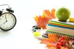 Fuentes de escuela, libro y despertador coloridos en blanco Cierre para arriba De nuevo a escuela Imagen de archivo